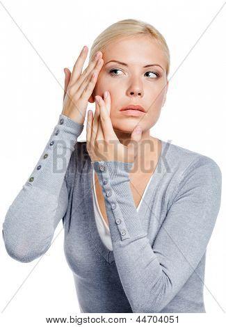 Señora examinar su cara y las arrugas que pueden aparecer, aislado en blanco
