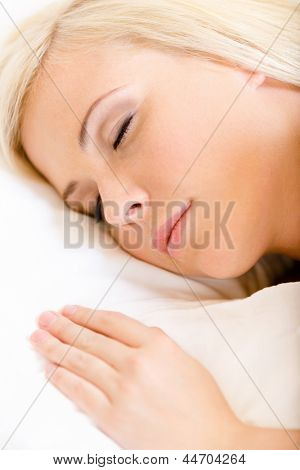 Close up of sleepy woman in bed lying on the white cushion