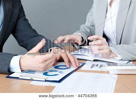 Two business people discuss economic issues sitting at the business table with documents