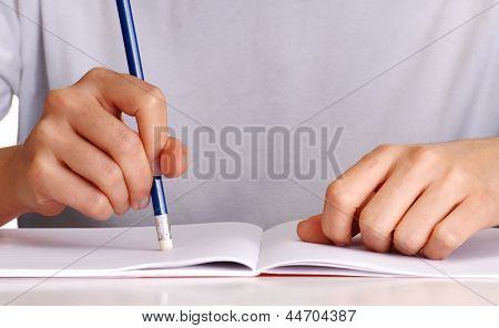 Holding pencil eraser rubbing out on notebook.