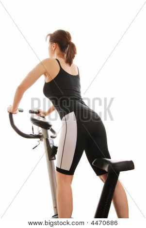 Isolated Young Woman Standing On A Bicycle
