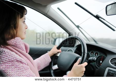 Young Woman Driving Car In Rain