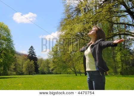 Woman Enjoys Sun In Spring Time Outdoors