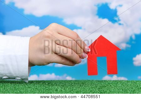 concept: woman hand with paper house on sky background, close up