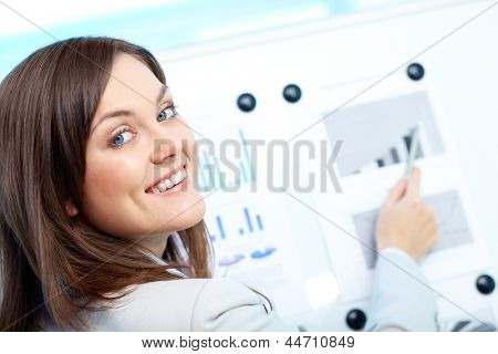 Portrait of a lovely young businesswoman looking at camera while presenting her project on board