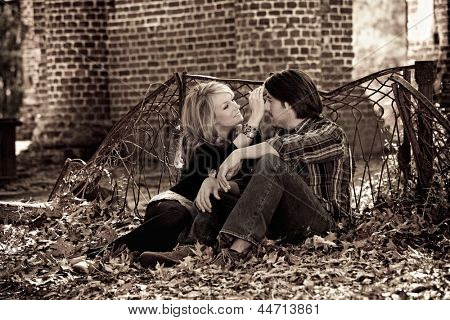 affectionate beautiful young couple in autumn leaves