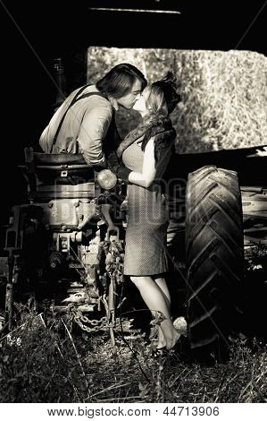 retro couple in 1940s clothing kissing on tractor