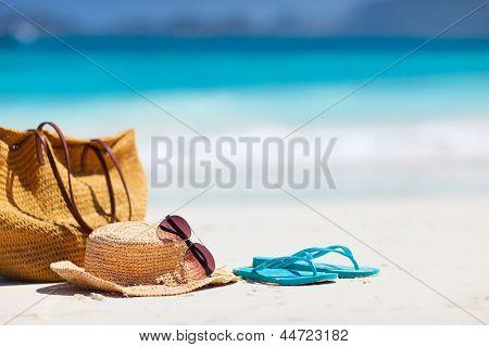 Chapéu de palha, bolsa, óculos de sol e falhanços da aleta em uma praia tropical