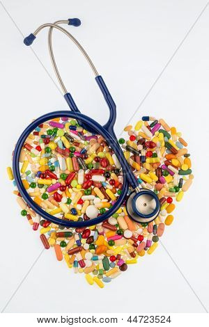 stethoscope and tablets in heart-shaped arrangement, symbol photo of heart disease, diagnosis and medication