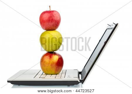 an apple is on a computer keyboard. symbolic photo for healthy and vitamin-rich snack.