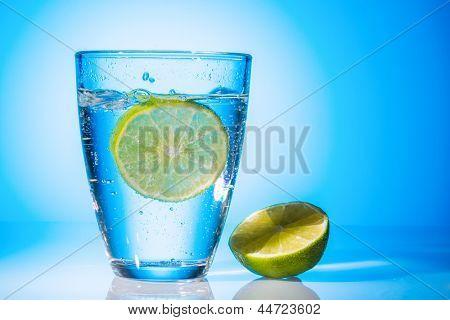 un vaso de agua fresca y un limón. agua mineral como un extintor de sed.