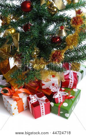 heap of  gift boxes  under decorated Christmas tree