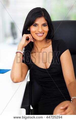 attractive young indian office worker sitting by office desk