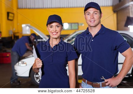 two happy auto service center employees portrait inside workshop