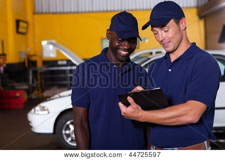 two happy auto mechanics going through checklist inside workshop