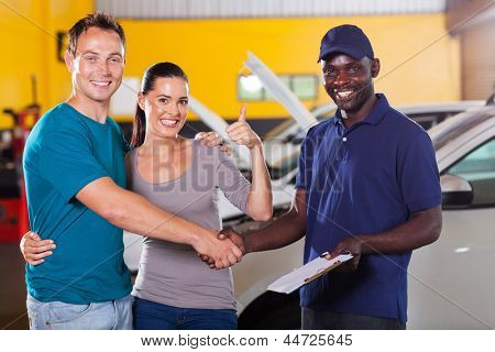 happy young couple giving thumb up to auto repair shop
