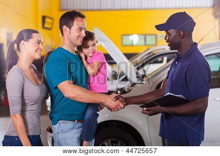 freundliche Auto Mechaniker Handshaking mit Familie in workshop