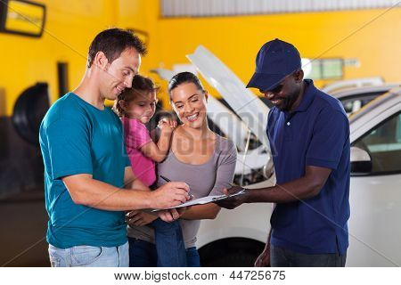 happy family man signing invoice in car repair shop