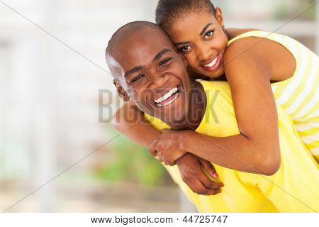 portrait of playful young african couple piggyback