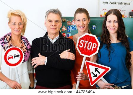 Driving school - driving instructor and student drivers look at a tempo thirty Road sign, in the background are traffic signs