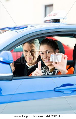 Driving School - Young woman steer a car, maybe she has a driving test, she holding proudly her driving license then she has passed