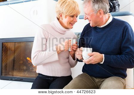 Seniors at home in front of fireplace with tea cup