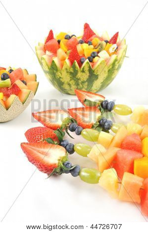 Fresh fruit salad of mango, strawberry, kiwi, grapes, strawberries blueberries banana in a bowl from watermelon honeydew and pineapple and fruit kebabs, brochette isolated on white