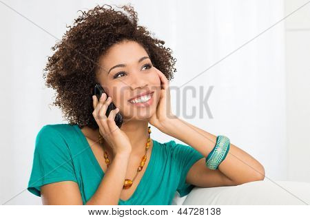Portrait Of Young Girl Talking On phone Sitting on Couch