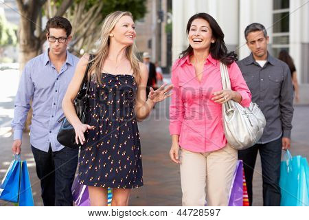 Two Couples With Bored Men Carrying Partners Bags
