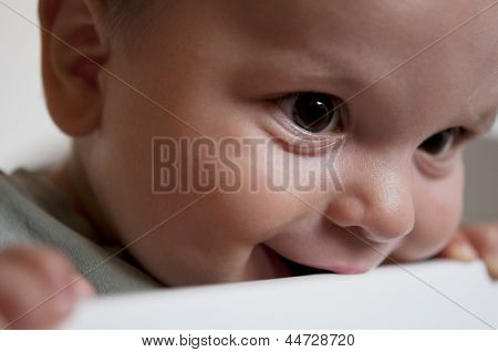 Close-up of a little Baby biting on crib