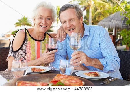Senior Couple Enjoying Meal In Outdoor Restaurant