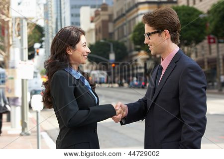 Businessman And Businesswoman Shaking Hands In Street
