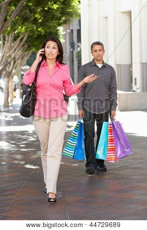 Fed Up Man Carrying Partners Shopping Bags On City Street