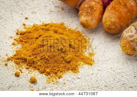 turmeric powder and root on a white painted rough barn wood surface