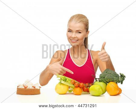 woman with fruits and cake pointing at healthy food