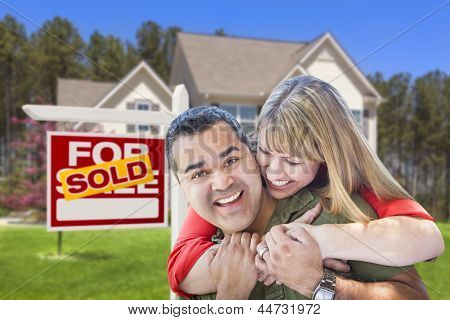 Happy Hugging Mixed Race Couple in Front of Sold Home For Sale Real Estate Sign and House.