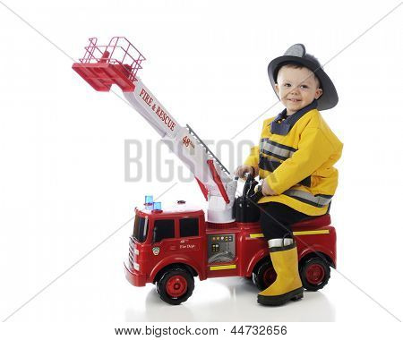 An adorable toddler happily playing fireman on his toy fire truck.  On a white background.