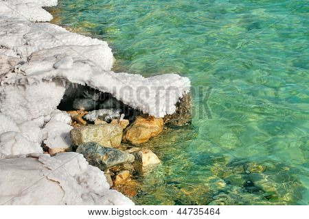 White salt formations on the rocks and aquamarine colored water of Dead Sea in Israel.