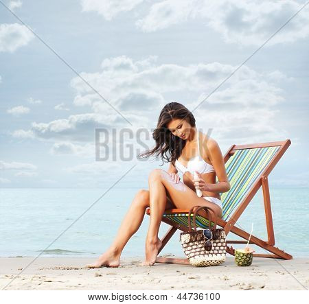 Beautiful, sporty and young woman in sexy swimsuit using cream on the beach