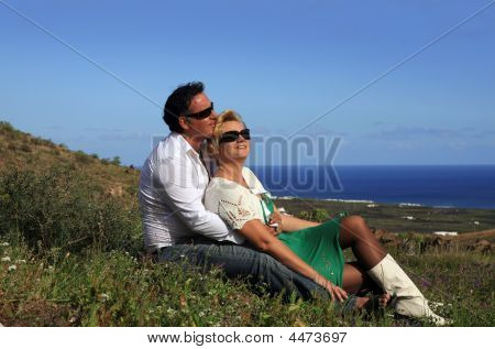 Spring In Lanzarote, Couple Sitting Outdoors Holding Flower Smiling