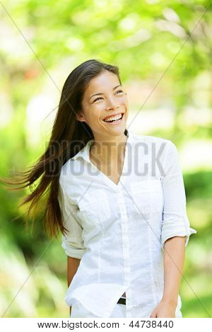 Joyful vivacious woman in a spring or summer park beaming a broad smile as she walks along rejoicing in the freshness of nature and the warm glow of the sunlight through the leaves of the green trees
