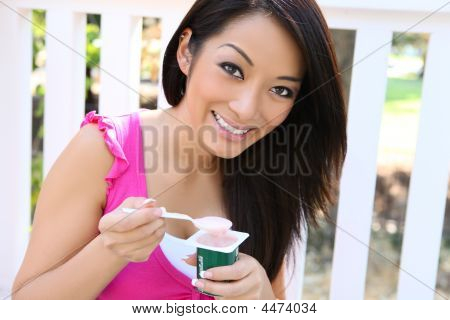 Pretty Asian Woman Eating Yogurt