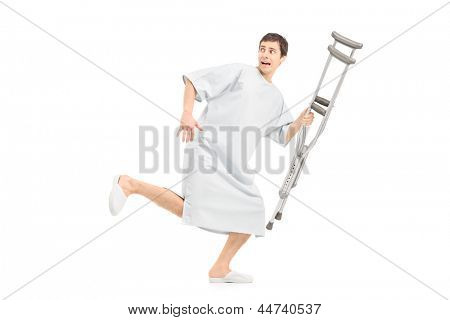 Full length portrait of a male scared patient running and holding a crutch, isolated on white background