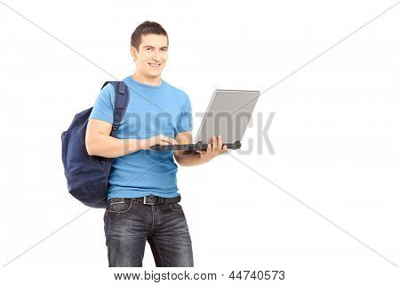 A male student with school bag working on a laptop and looking at camera isolated on white background