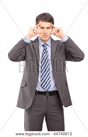A young businessman holding his head in pain as a result of a headache isolated against white background
