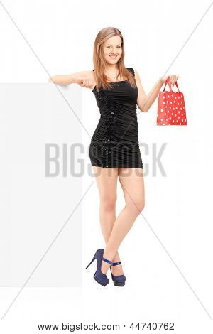 Full length portrait of a young female with a gift bag standing next to a blank panel, isolated on white background