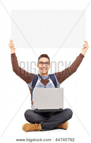 Smiling male student sitting with laptop and holding a blank panel, isolated on white background