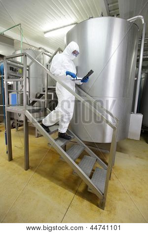 scientist in uniform focused on tablet, walking down the stairs