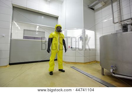 professional in protective uniform standing in industrial environment