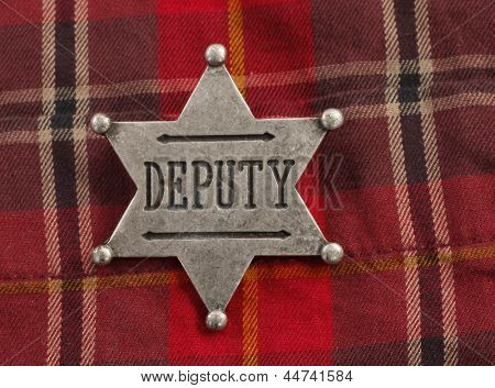 Deputy star badge attached on red plaid cowboy shirt